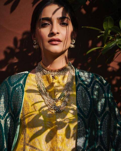 A little gold choker adds shine above the beautiful, multi-layer pearls necklace that matches the earrings - Fashion Models