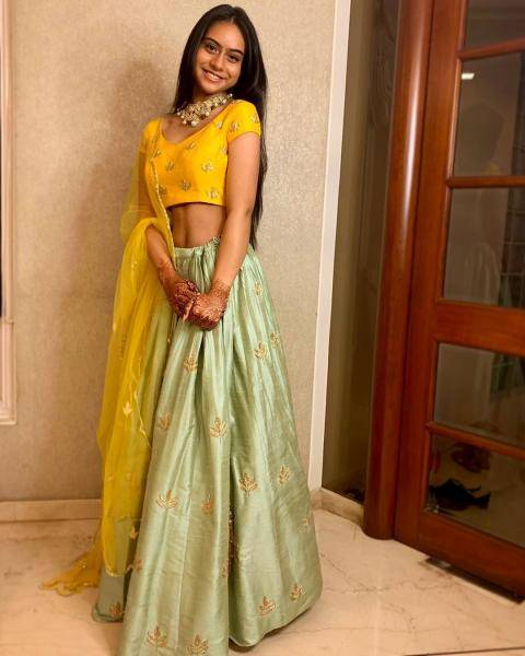 The sea green silk lehenga with motif embroidery is woprn wth a matching yellow top and a yellow tulle shawl - Fashion Models